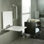 Taburetes y asientos de ducha plegables realizados con resina técnica reforzada en co-inyección, y aluminio resistente a la corrosión